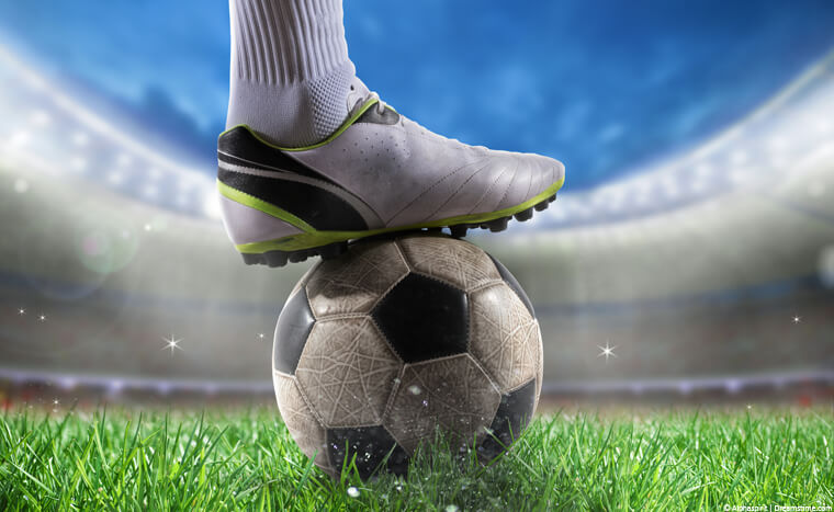 Footballer's foot standing on ball