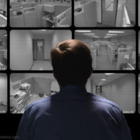 Man sitting in front of surveillance monitors