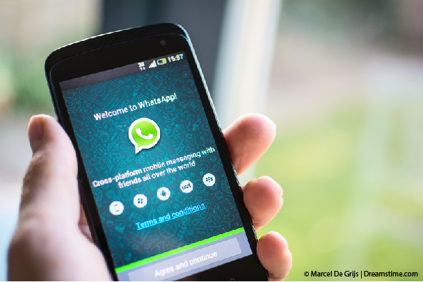 Man holding phone with WhatsApp open