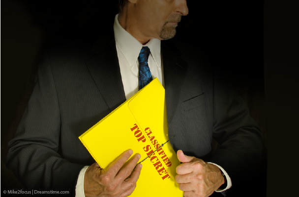 Man in a suit with a classified folder