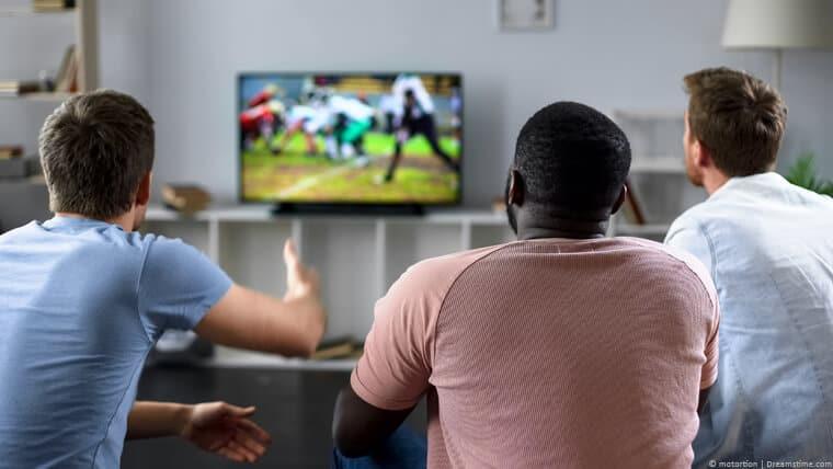 Three men watching sport on TV