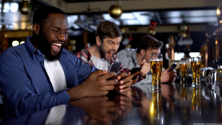 Three friends in the pub winning on their phones