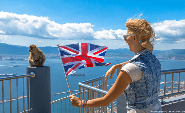 Lady holding UK flag next to Gibraltar monkey