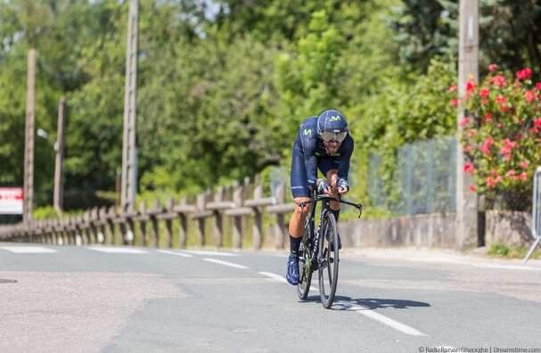Professional cyclist in blue passing green trees