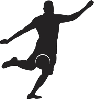 Silhouette of football player kicking ball