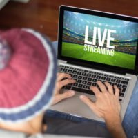 Man watching live sport on laptop