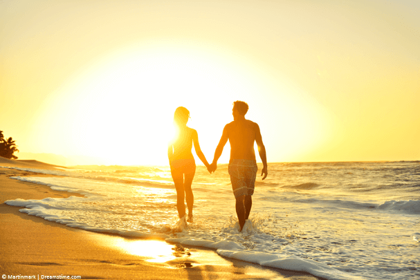 Couple holding hands walking on the beach