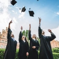 Four university students throwing mortarboards in the air