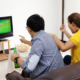 Asian man and women watch football on TV