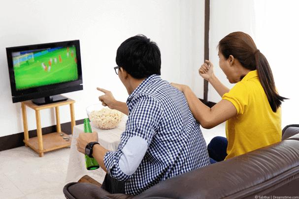 Asian man and women watch football on TV