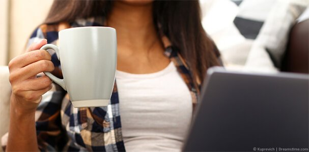 Women watching 9Now on laptop holding cup