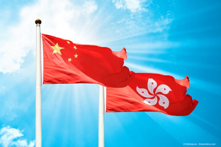 The flags of Communist China and Hong Kong flying in front of a blue sky.