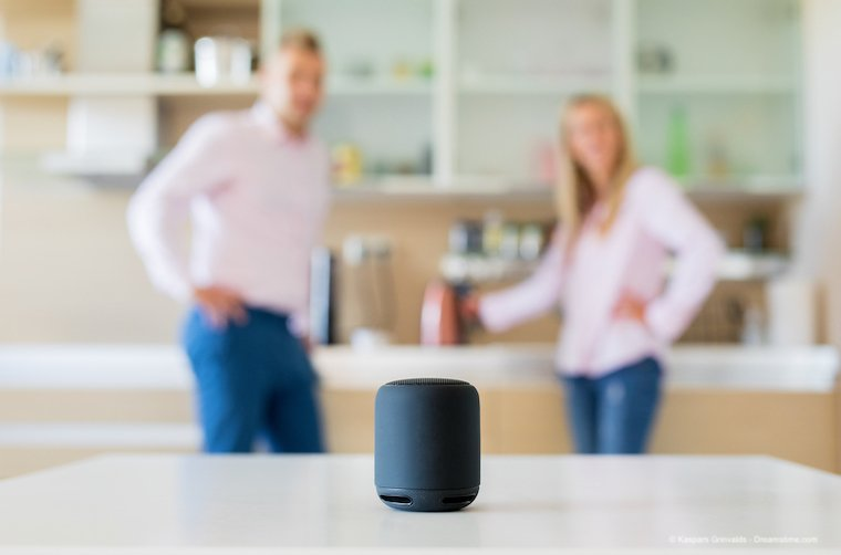 Couple using smart speaker at home