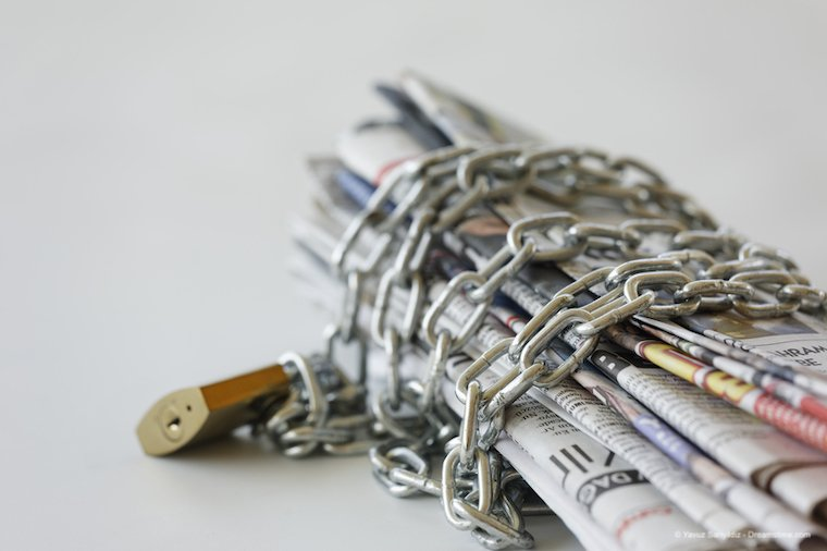 A bundle of newspapers in chains illustrating media censorship
