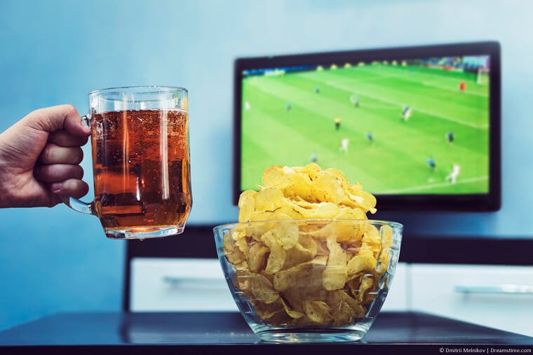 Football on TV with beer and chips on table