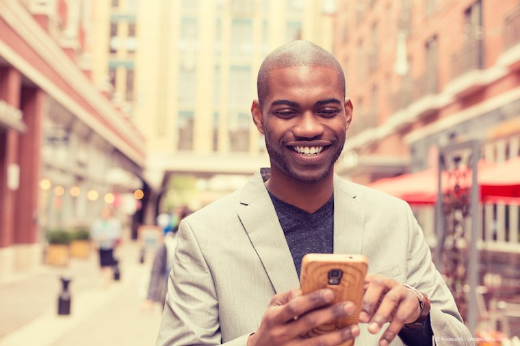 A smiling African man using a VPN on his smartphone