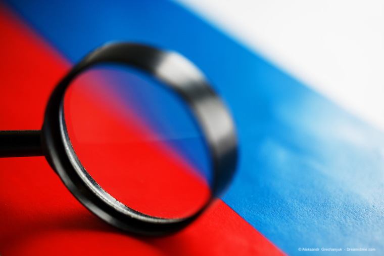 The flag of the Russian Federation is viewed through a magnifying glass.
