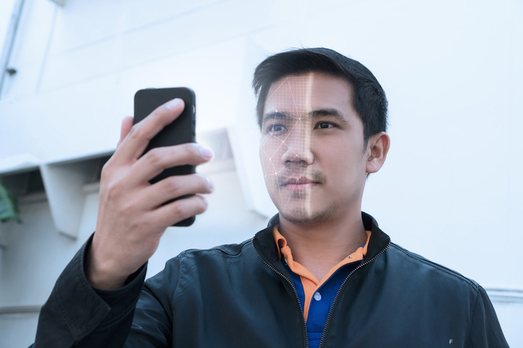 Biometric facial recognition on smartphone. Unlock smartphone as it scans his face.