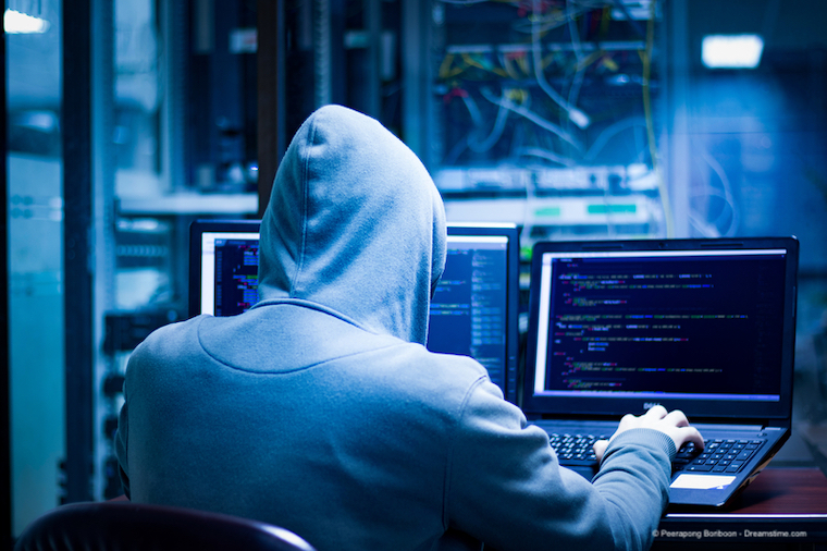 A hacker at work wearing a hoodie