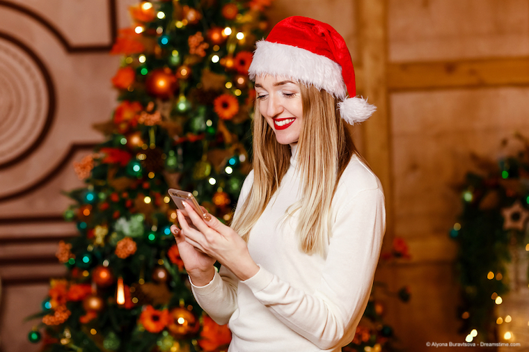 woman on smartphone in front of Xmas tree