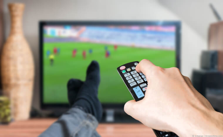 Hand with remote control watching football on TV