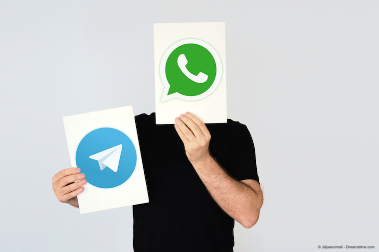 Man holding Telegram and WhatsApp logos