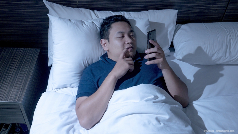 Man lying in bed watching porn on a smartphone
