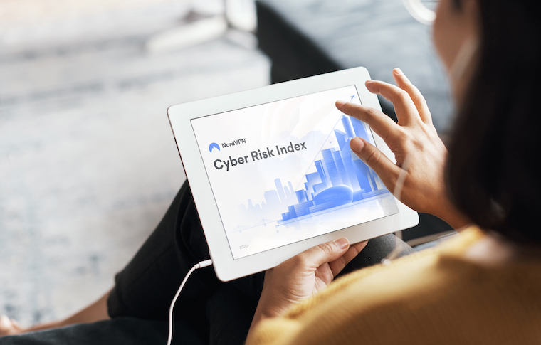 Woman reading NordVPN Cyber Risk index on tablet