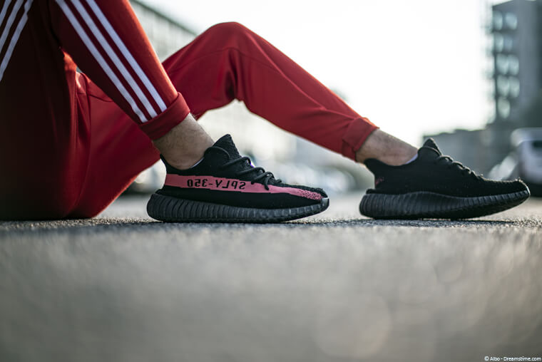 Man wearing Yeezy sneakers with red adidas track pants.