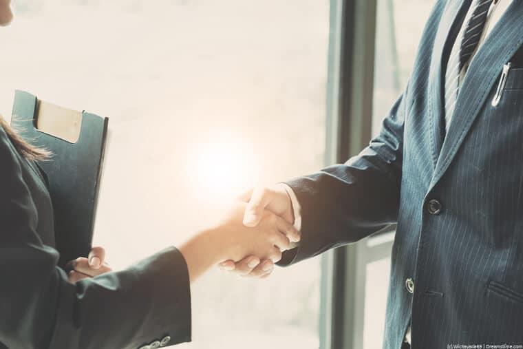 Businesswomen and man shaking hands